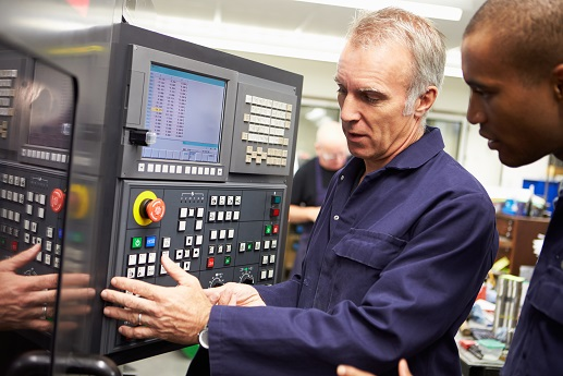Engineer Teaching Apprentice To Use Computerized Lathe